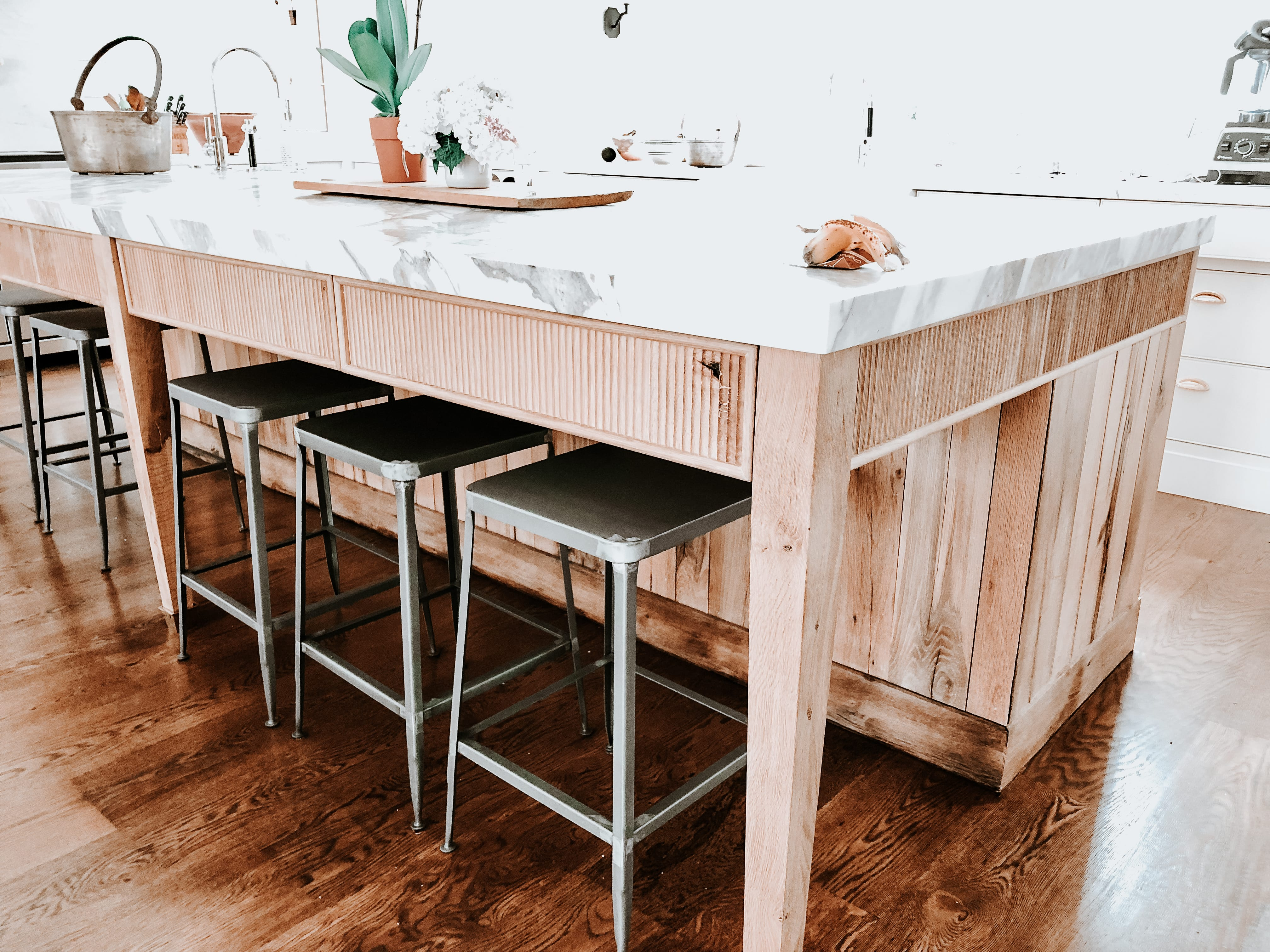 Fluted Wooden Cabinets with white marble countertops