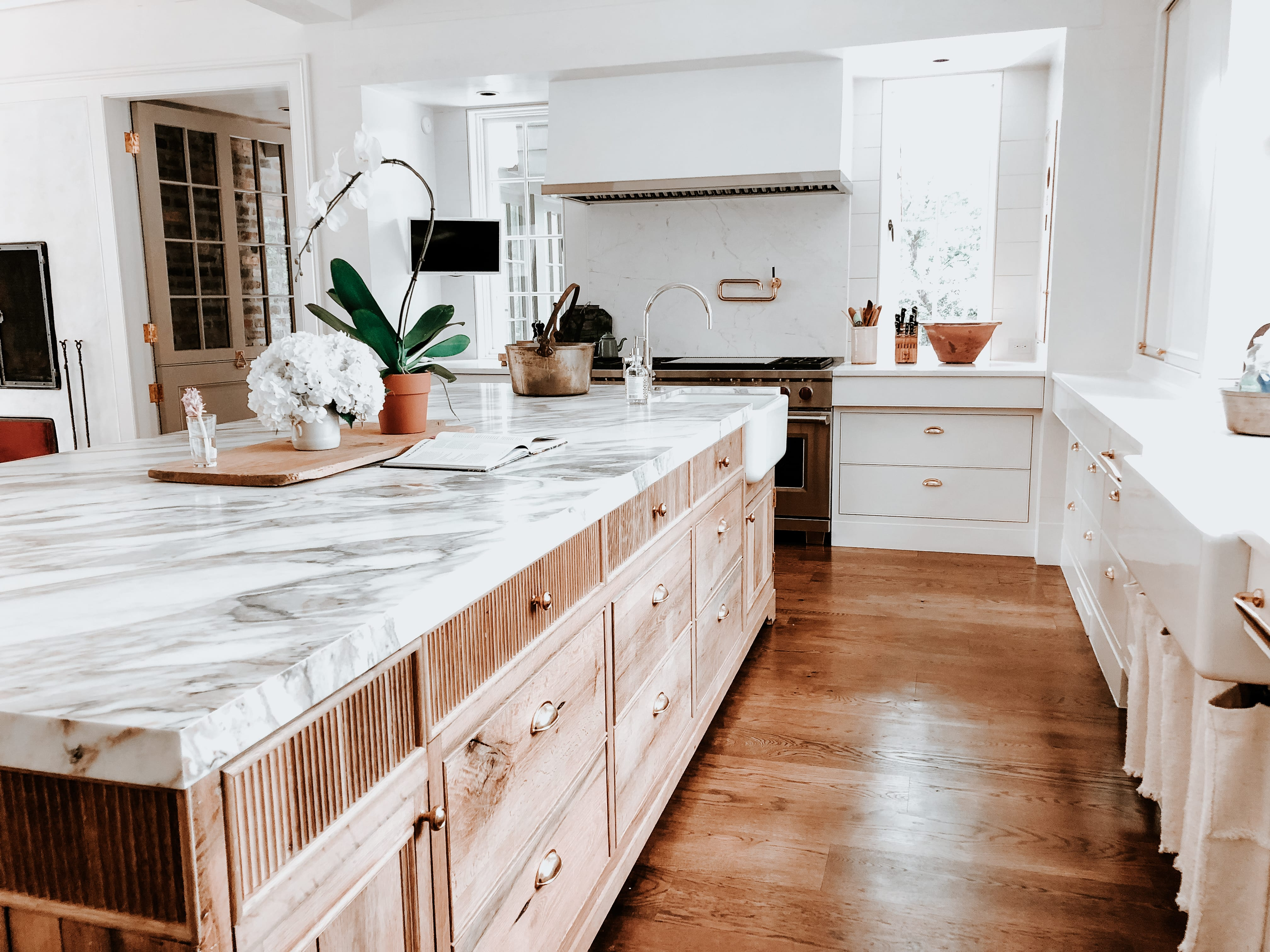 Modern White kitchen with fluted wooden cabinets